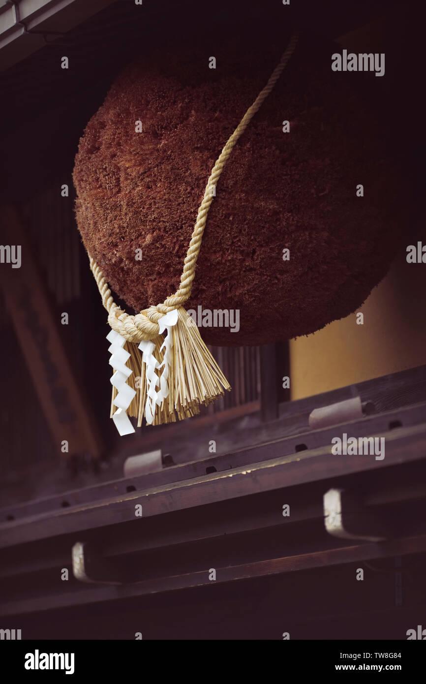 Sugidama, cedar ball, with Shinto Shimenawa rope tied around it, hanging above the entrance of a sake brewery in Hida-Takayama, Japan - Stock Image