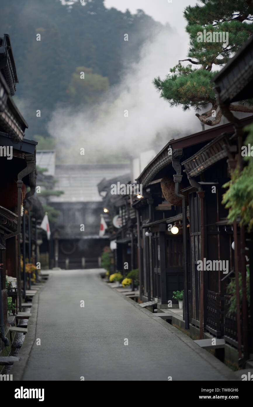 Kamisannomachi, old town street of Takayama city in a tranquil early morning scenery with steam coming from a sake brewery shop. - Stock Image