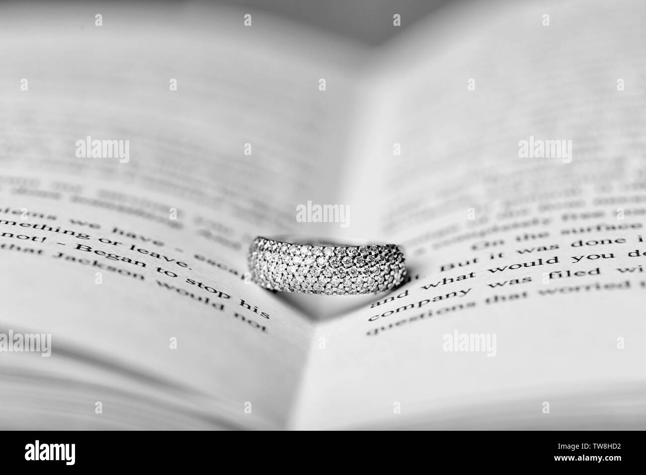 Engagement ring between pages of book, closeup - Stock Image