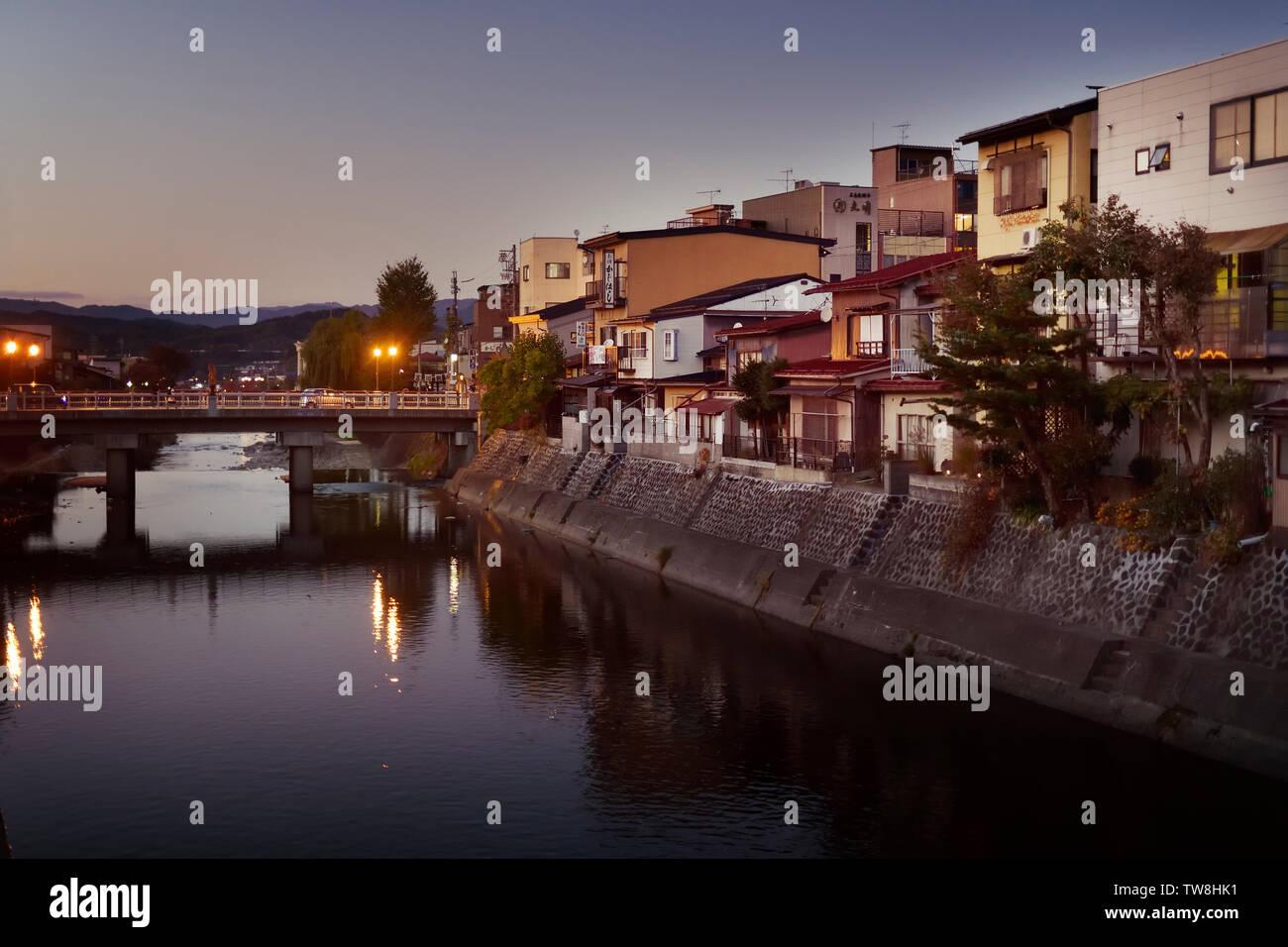 Row of houses on a bank of Miyagawa river, Takayama in a sunset city scenery. Hida-Takayama, Gifu prefecture, Japan 2018. - Stock Image