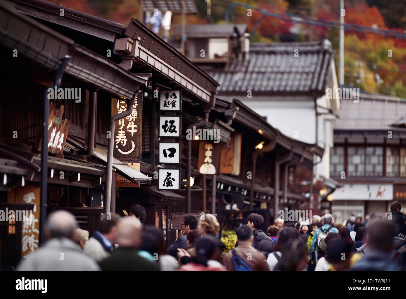 Signs of shops and restaurants at Kami-Sannomachi, old town market street of Takayama city busy with tourists and visitors in autumn. Kamisannomachi i - Stock Image