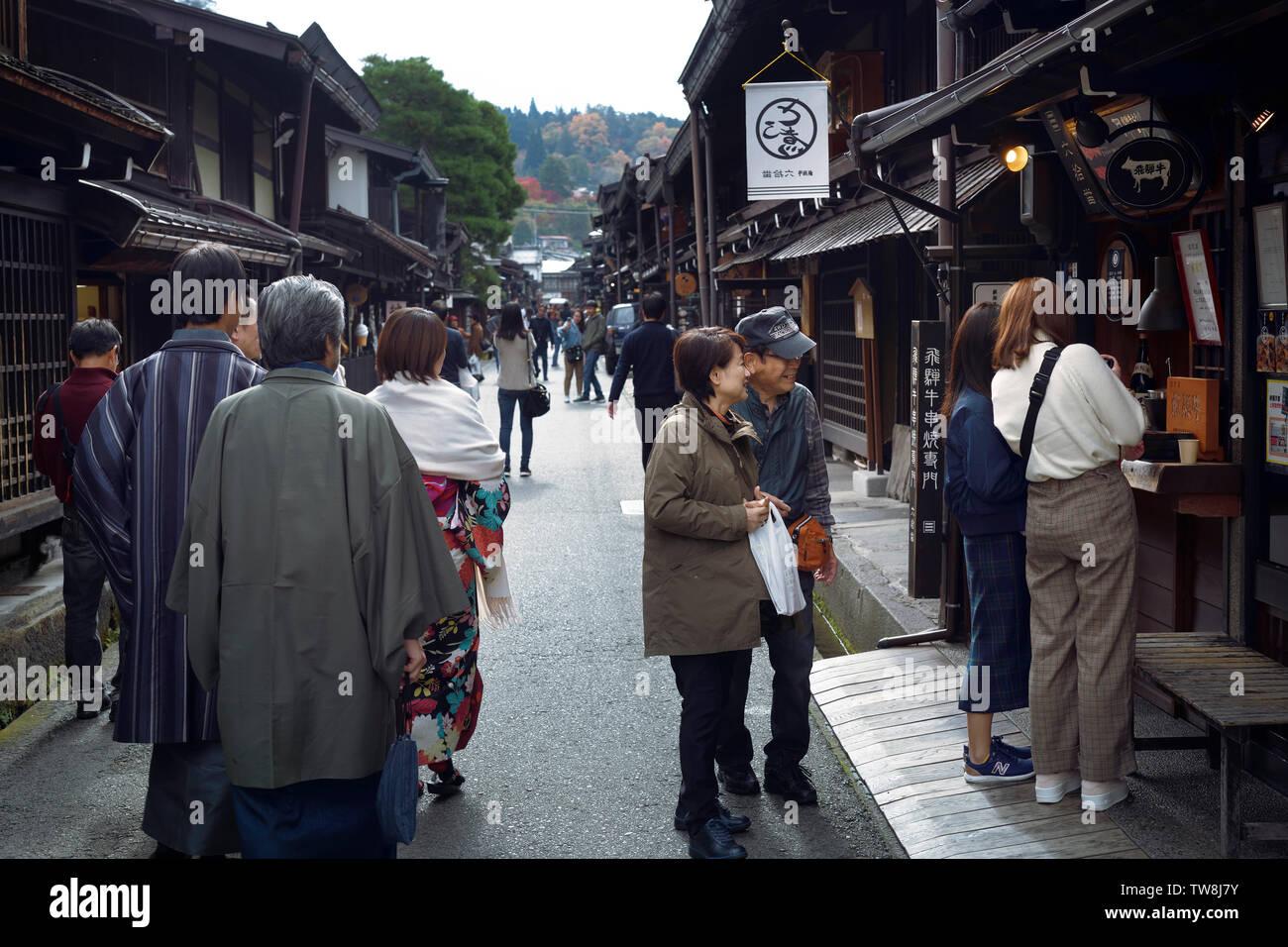 Busy with tourists old town market street of Takayama city. Kamisannomachi merchant town lined with shops and restaurants. Hida-Takayama, Gifu prefect - Stock Image