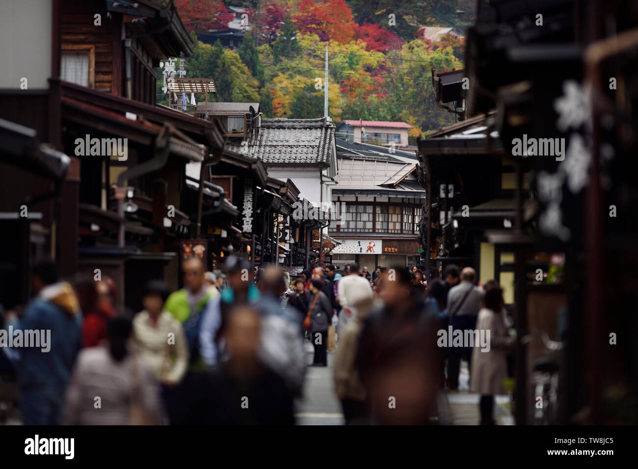 Shops and restaurants at Kami-Sannomachi, old town market street busy with tourists and visitors in autumn city scenery of Takayama, Gifu, Japan 2018. - Stock Image