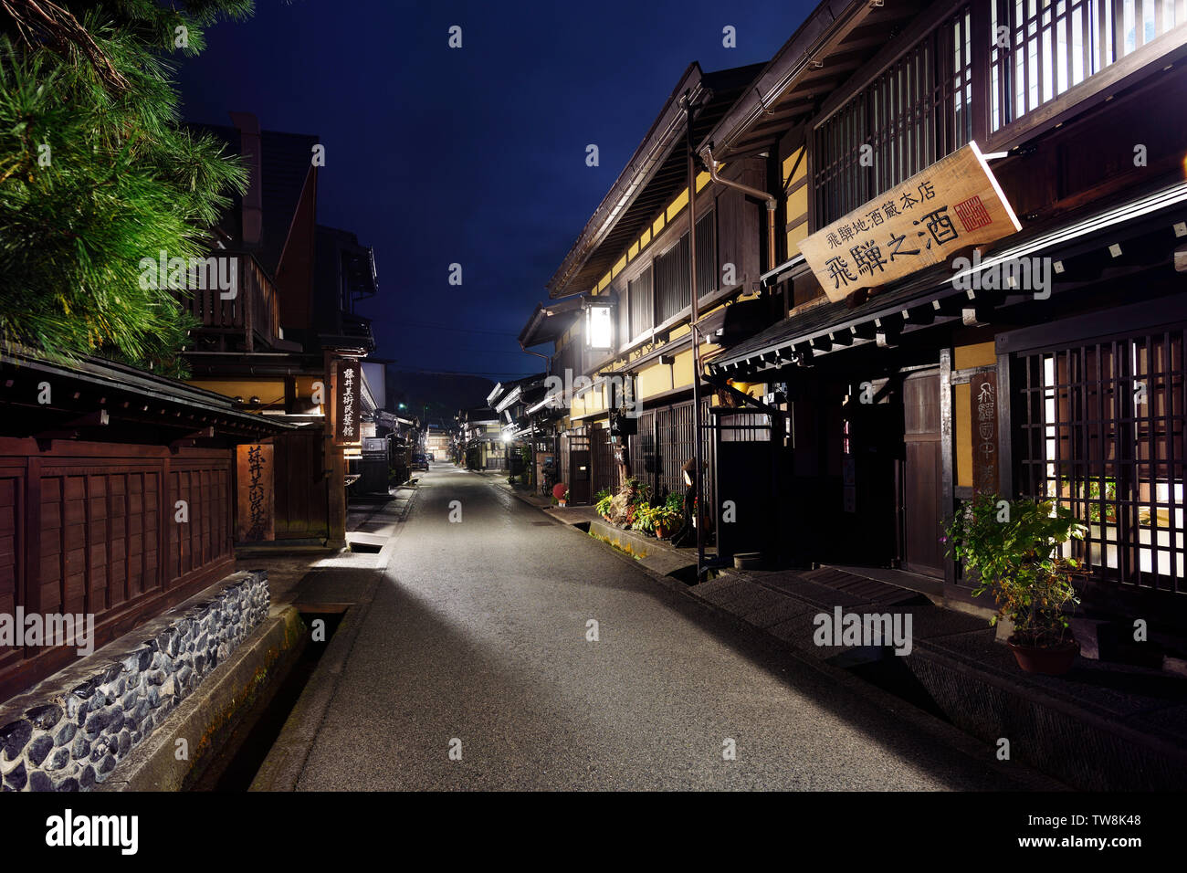 Nighttime scenery of Kamisannomachi, old town street of Takayama city, with lit up street lights and store signs. Kamisannomachi is a merchant town st - Stock Image