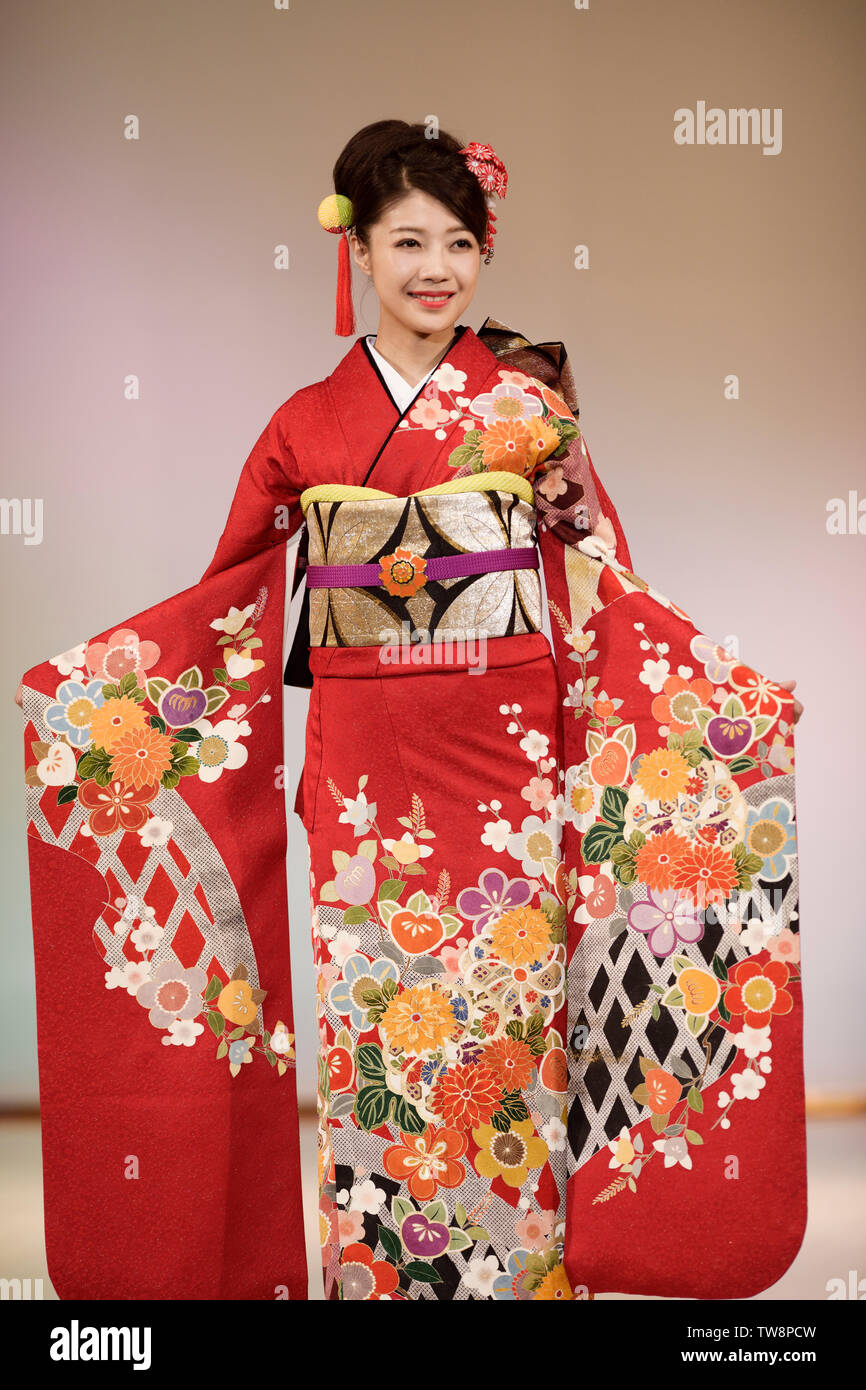 74b460a9f Young Japanese woman in a beautiful bright red kimono with a colorful  floral pattern, golden