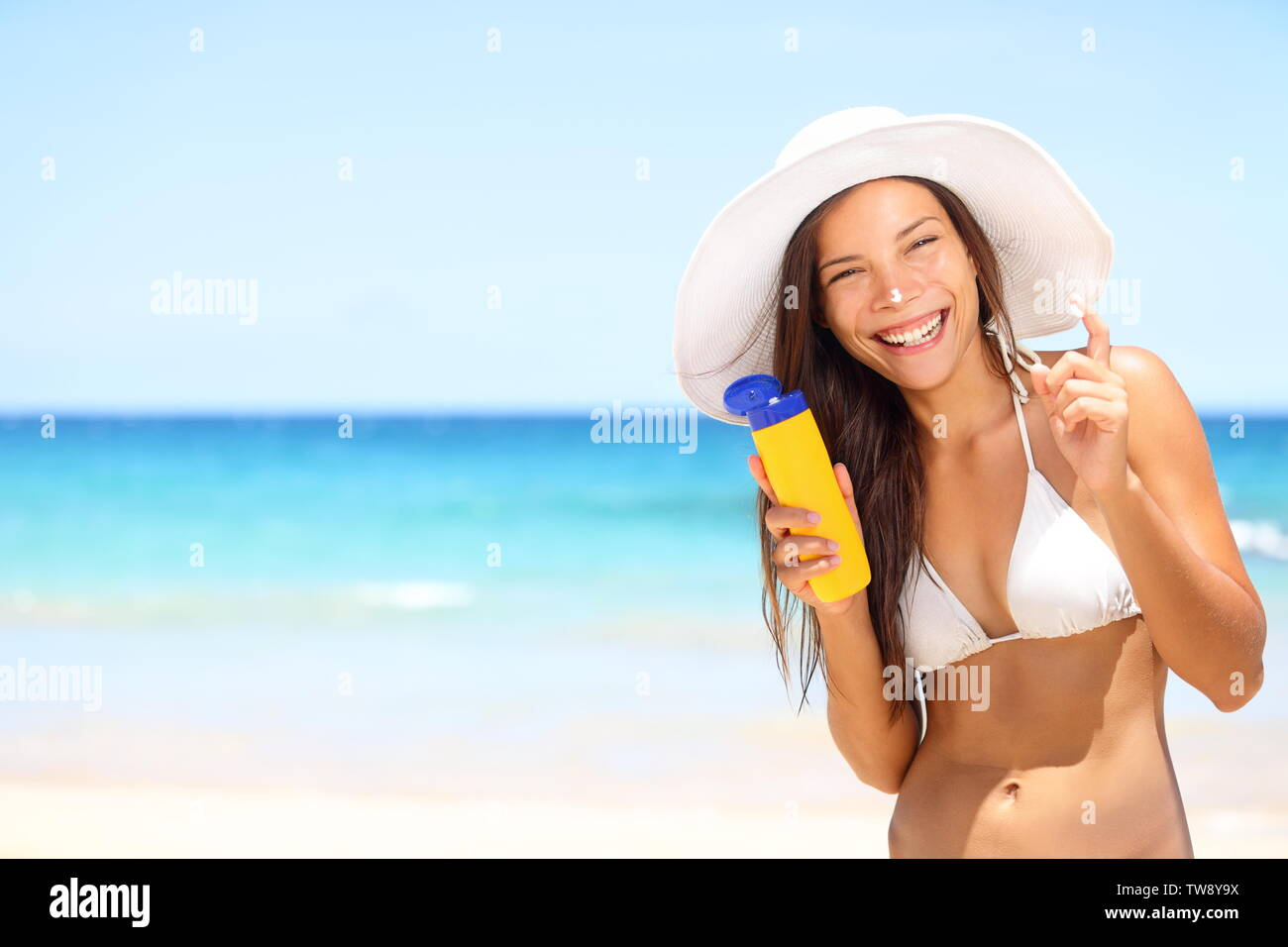 Sunscreen beach woman in bikini applying sun block solar cream for UV protection. Girl smiling to camera, wearing white sun hat, happy on vacation travel holiday. Hawaii, USA Stock Photo