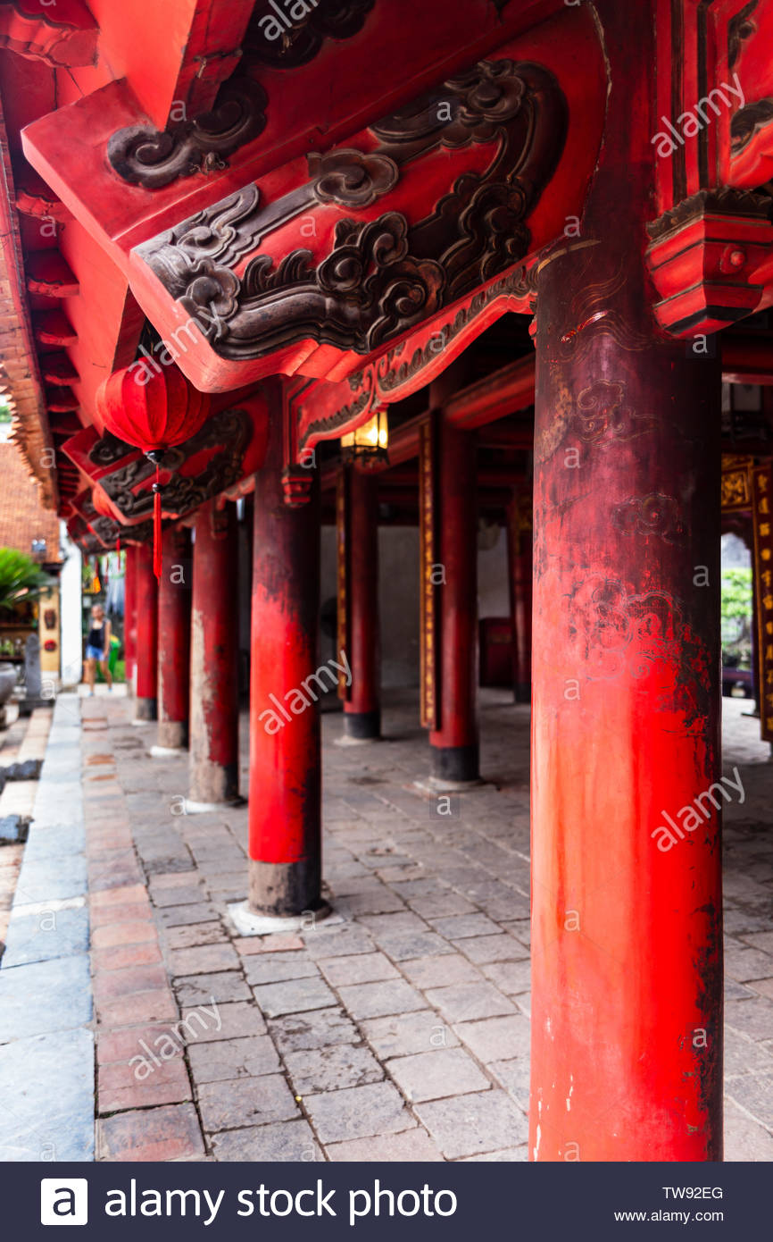 Perspective of red wooden roof beams and pillars with traditional black engravings close-up in the Temple of Literature (Quoc Tu Giam), Hanoi, Vietnam Stock Photo
