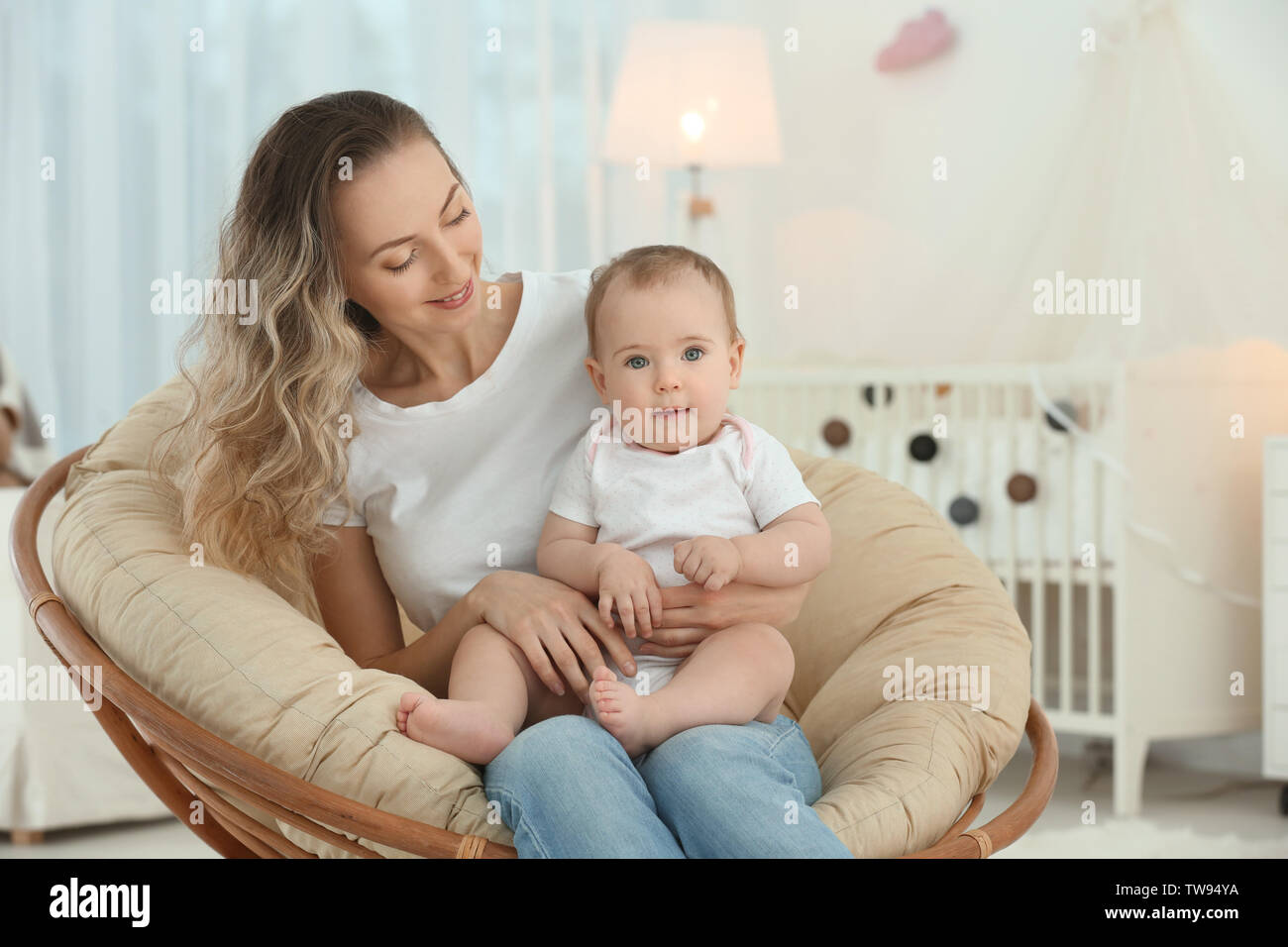 Young Mother With Her Cute Little Baby In Lounge Chair At Home Stock Photo Alamy