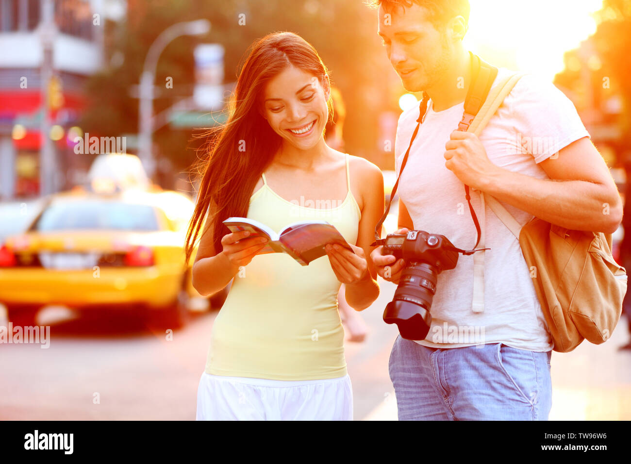 Travel tourist couple traveling in New York reading guide book standing with SLR camera at sunset on Manhattan with yellow taxi cab in the background. Happy young multiracial couple on summer holidays - Stock Image
