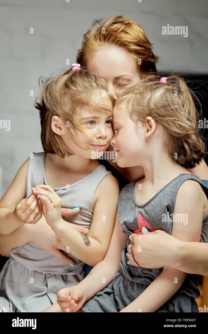 Two little beautiful twin girls with mum cuddle at home on gray background - Stock Image