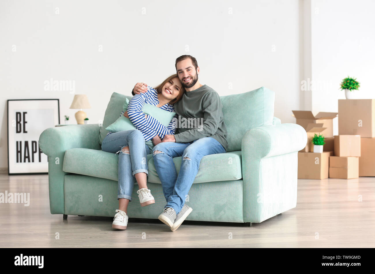 Young couple sitting on sofa after moving to new home - Stock Image