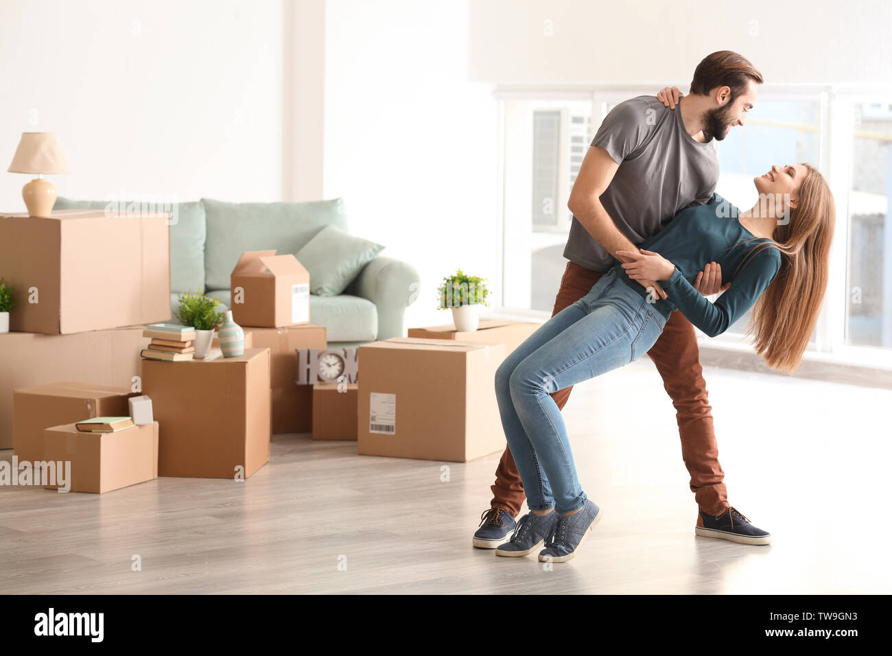 Young happy couple in room with moving boxes at new home - Stock Image