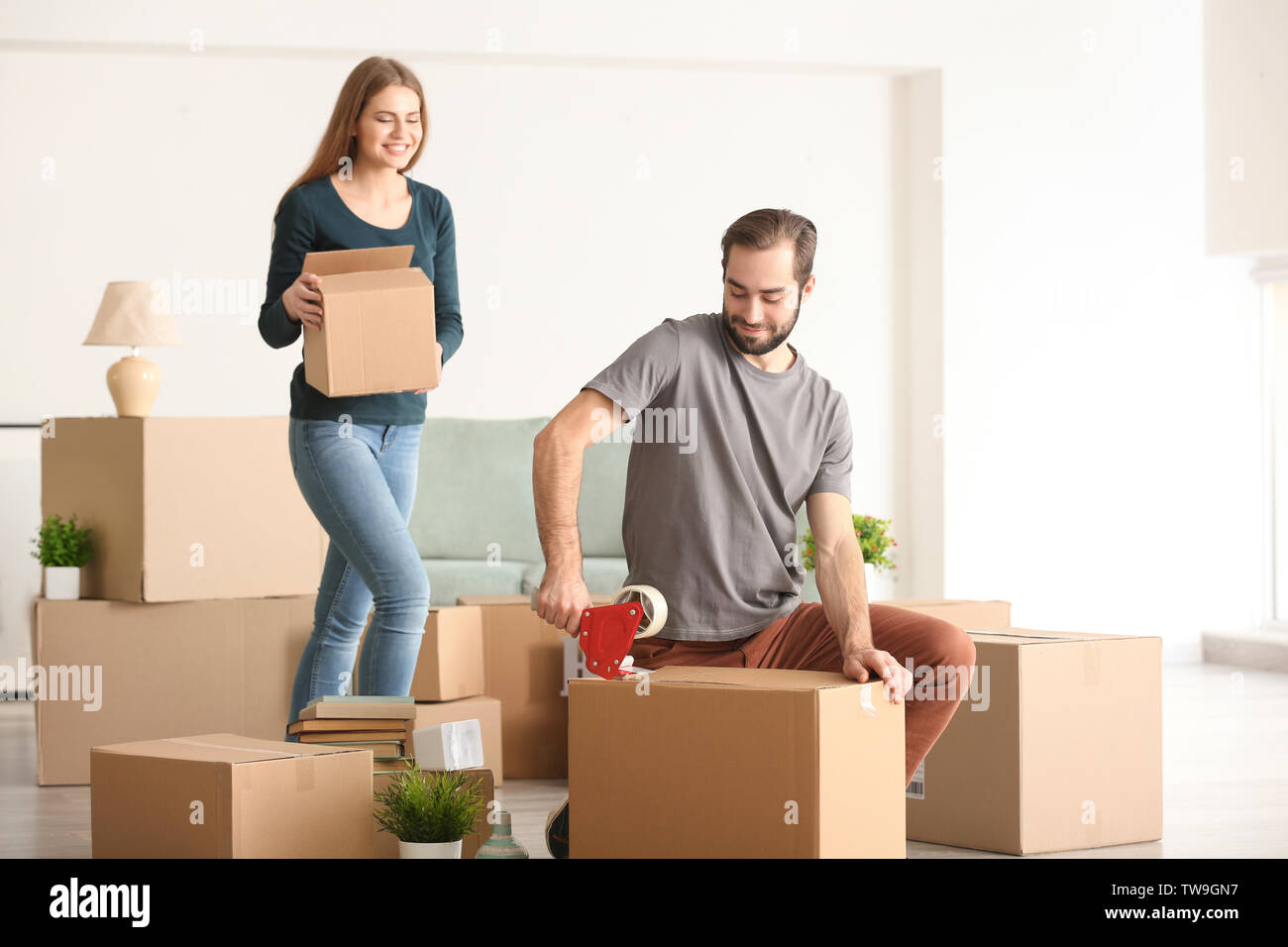 Young couple packing moving boxes, indoors - Stock Image