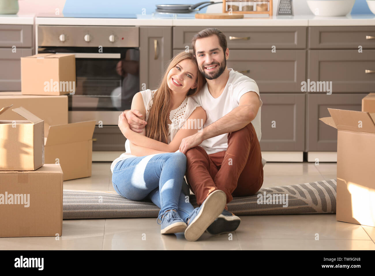 Young couple with moving boxes on floor in kitchen at new home - Stock Image