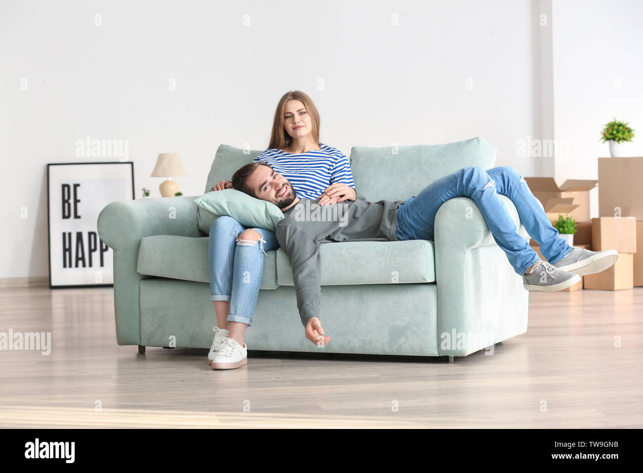 Young couple resting on sofa after moving to new home - Stock Image