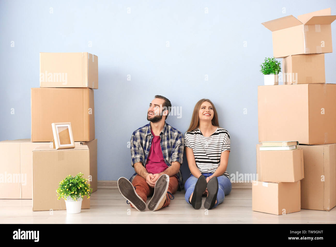 Young couple with moving boxes on floor in room - Stock Image