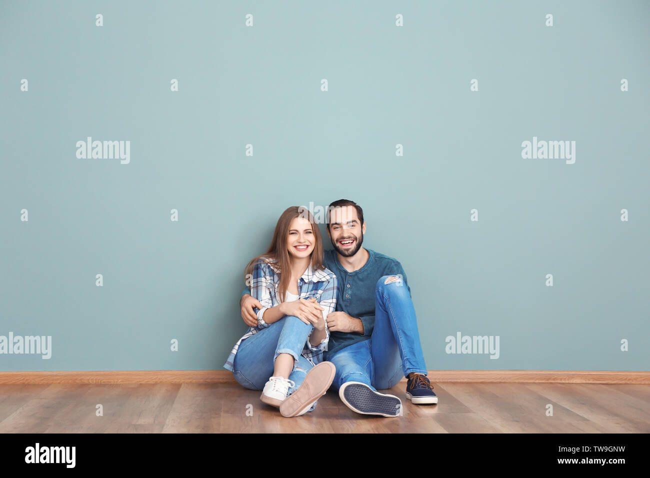 Young couple sitting on floor in empty room. Ready for moving to new house - Stock Image