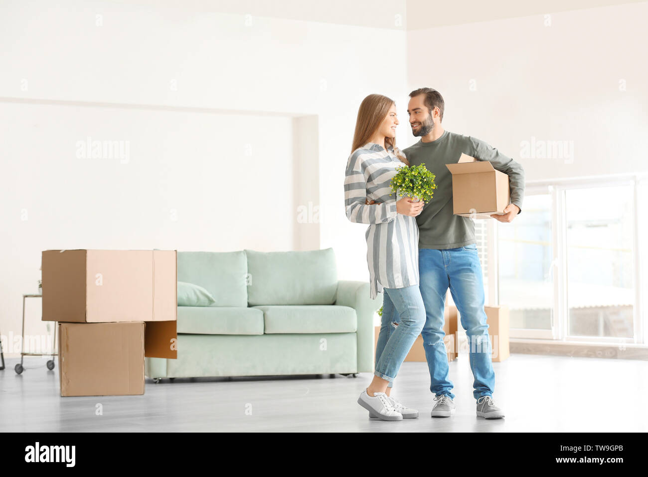 Young man holding moving box and woman with houseplant in room at new home - Stock Image