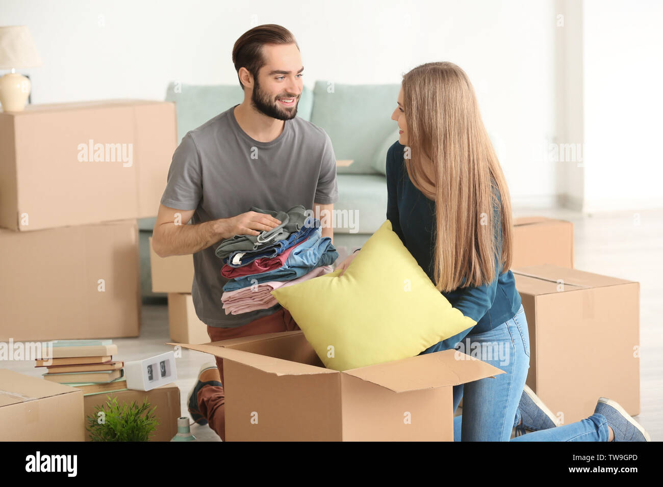 Young couple packing moving boxes in room - Stock Image