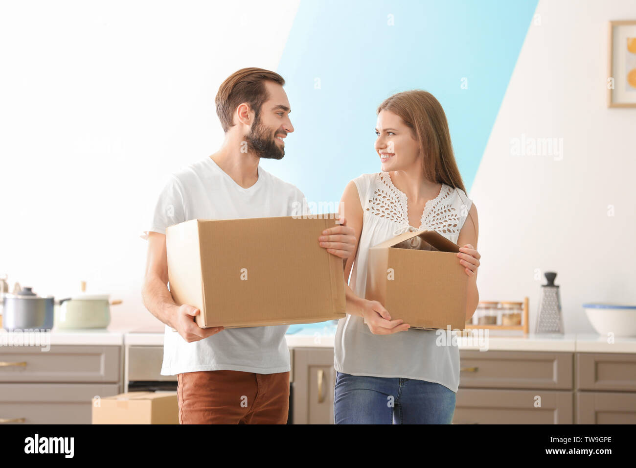 Young couple with moving boxes in kitchen at new home - Stock Image