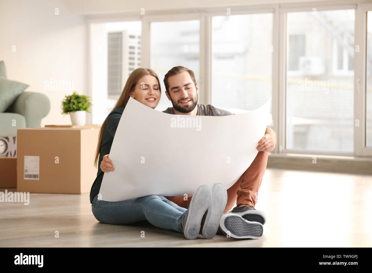 Young couple with house plan sitting on floor after moving to new home - Stock Image