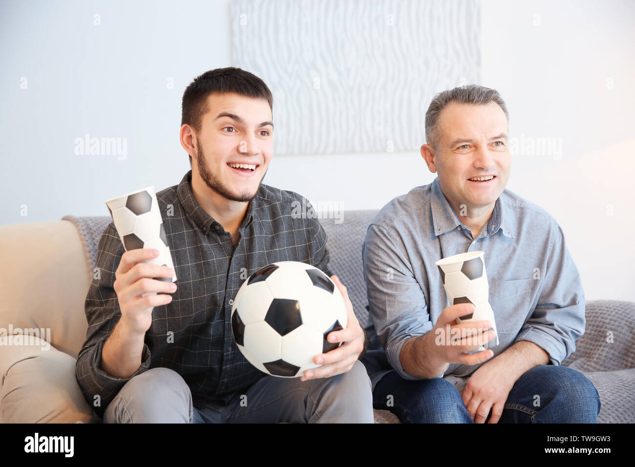 Mature man and his son watching football match on TV at home - Stock Image