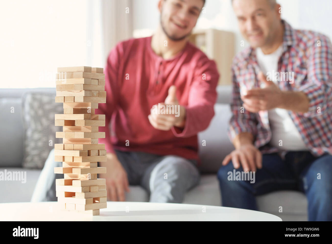Board game and blurred men on background. Dad and son spending time together - Stock Image