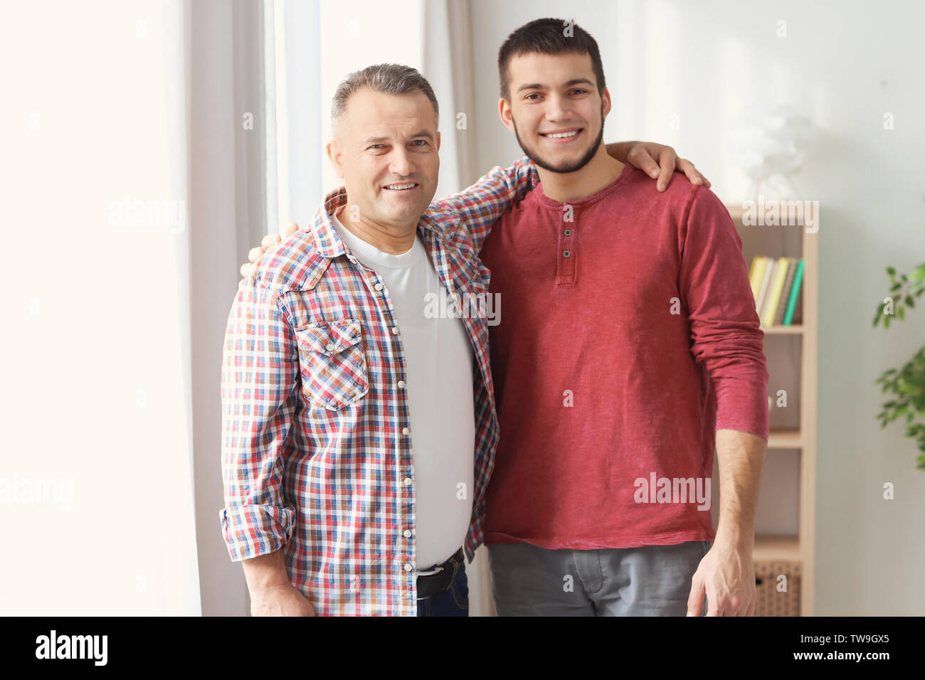 Mature man and his son at home - Stock Image