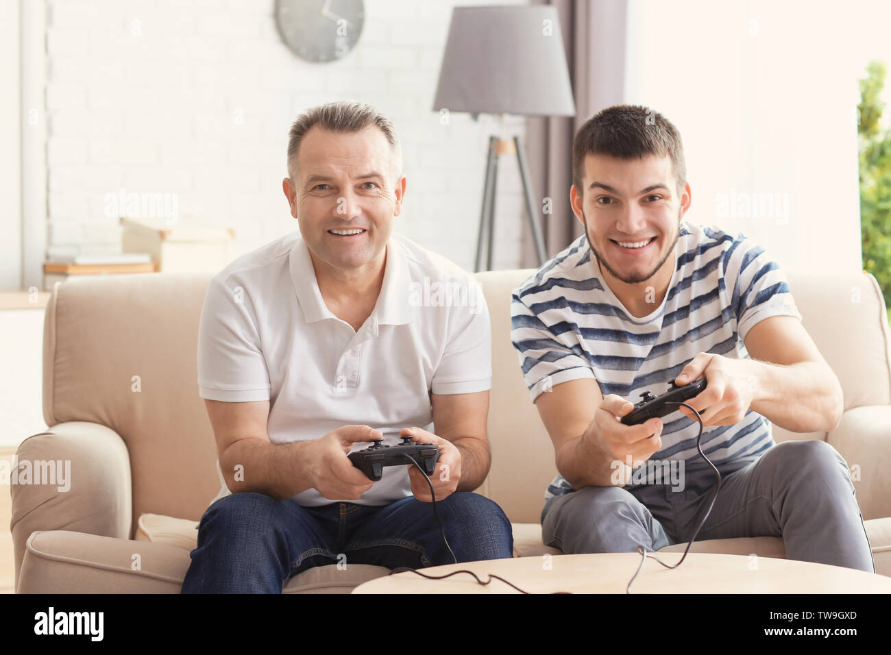 Mature man playing video game with his son at home - Stock Image