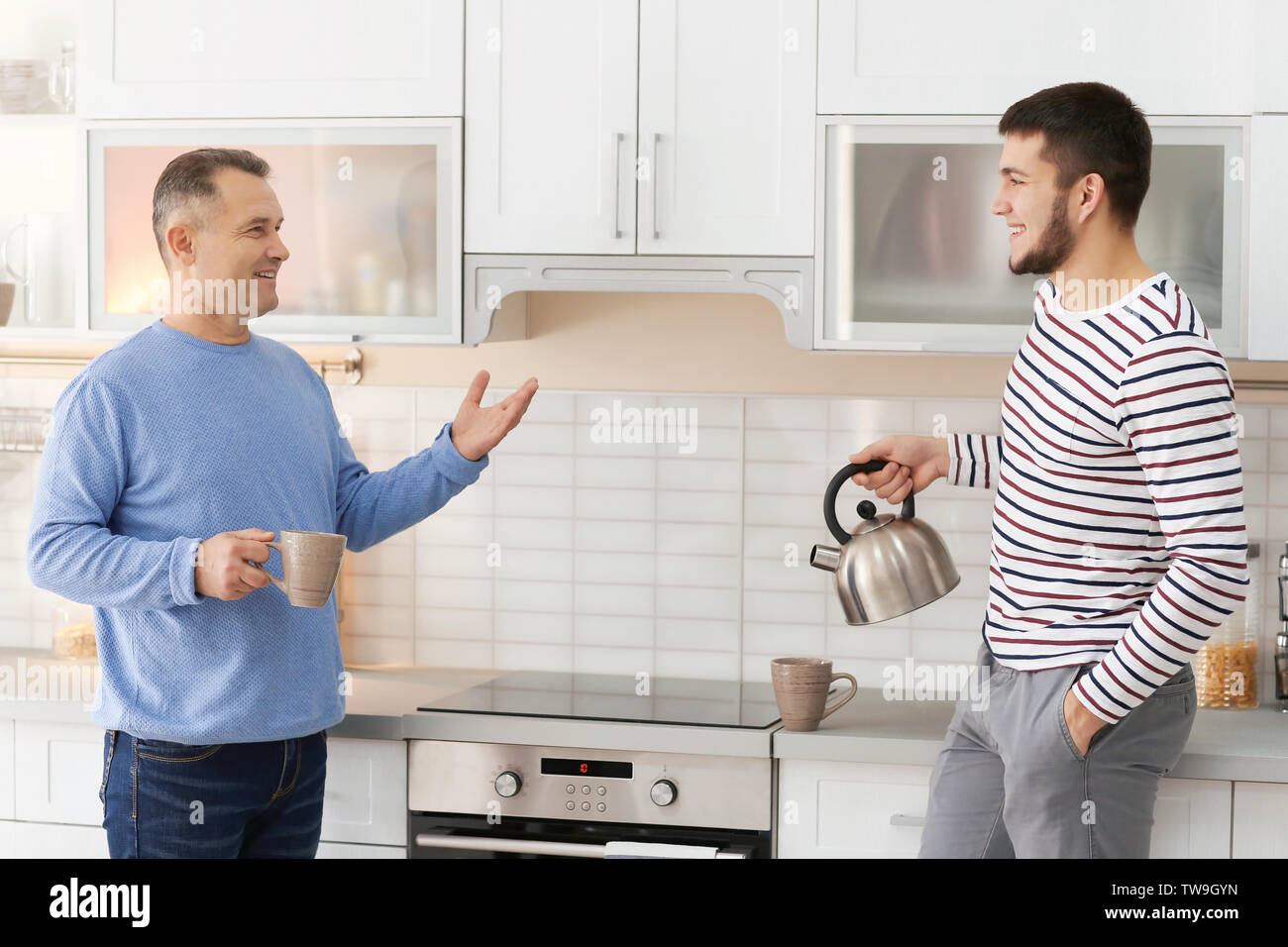 Mature man spending time with his son at home - Stock Image
