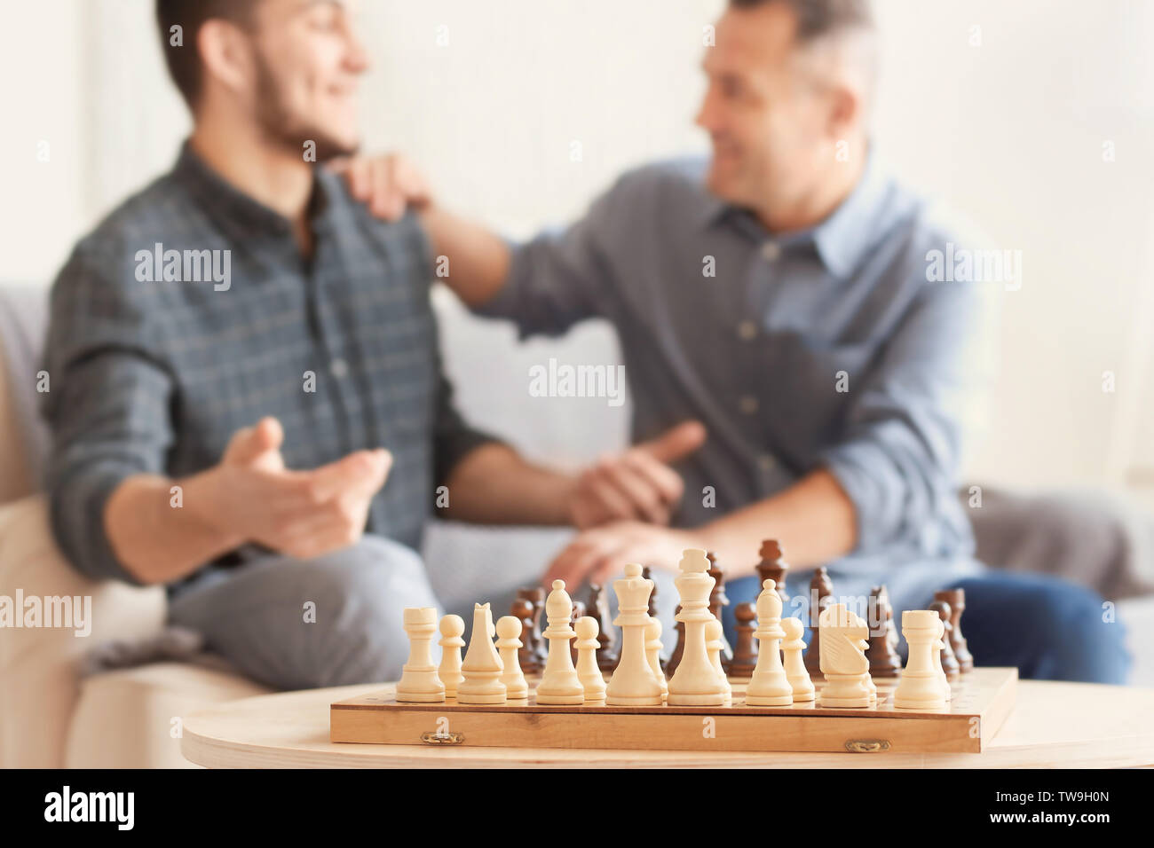 Chess board and blurred men on background. Dad and son spending time together - Stock Image