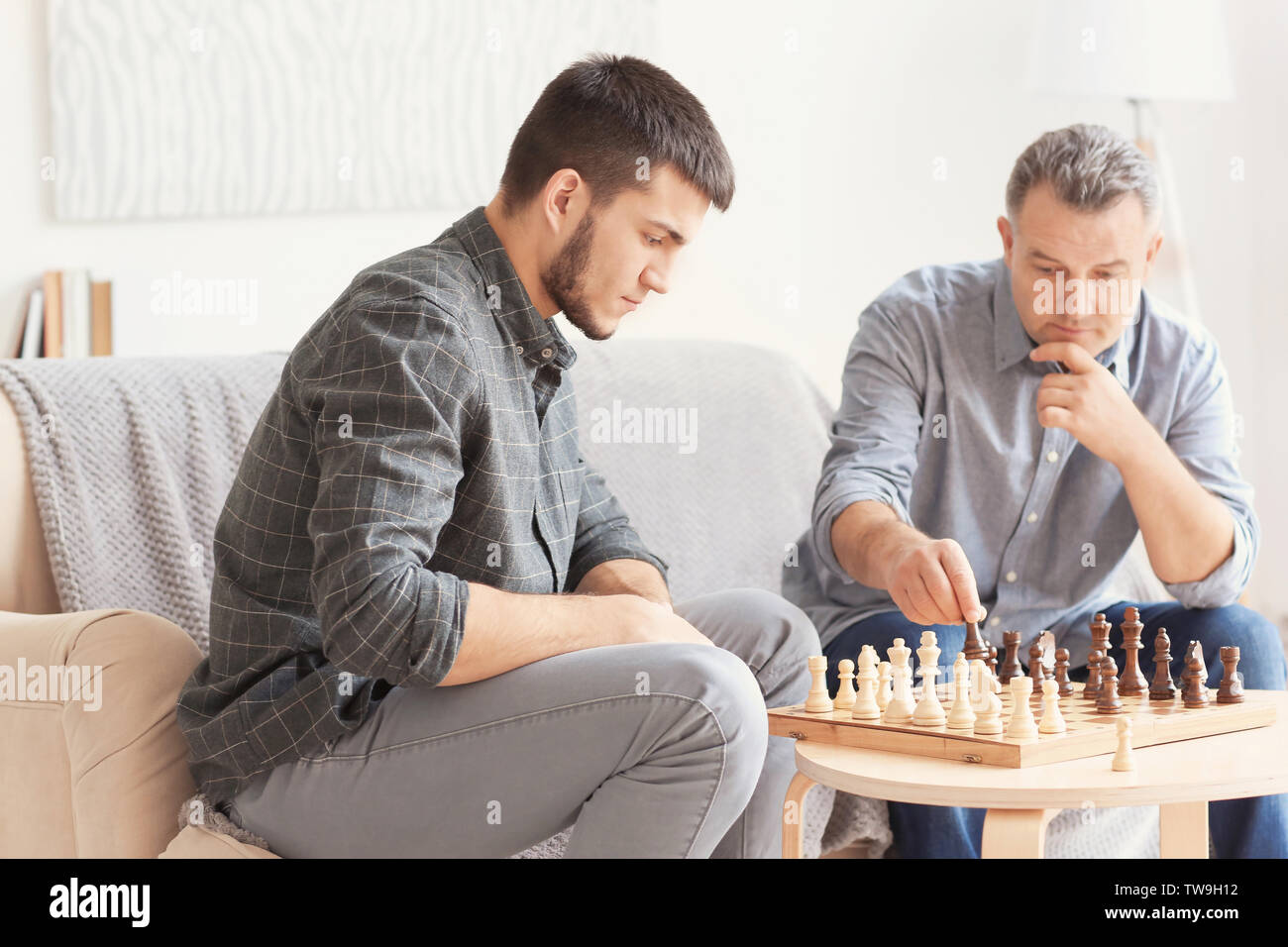 Mature man playing chess with his son at home - Stock Image