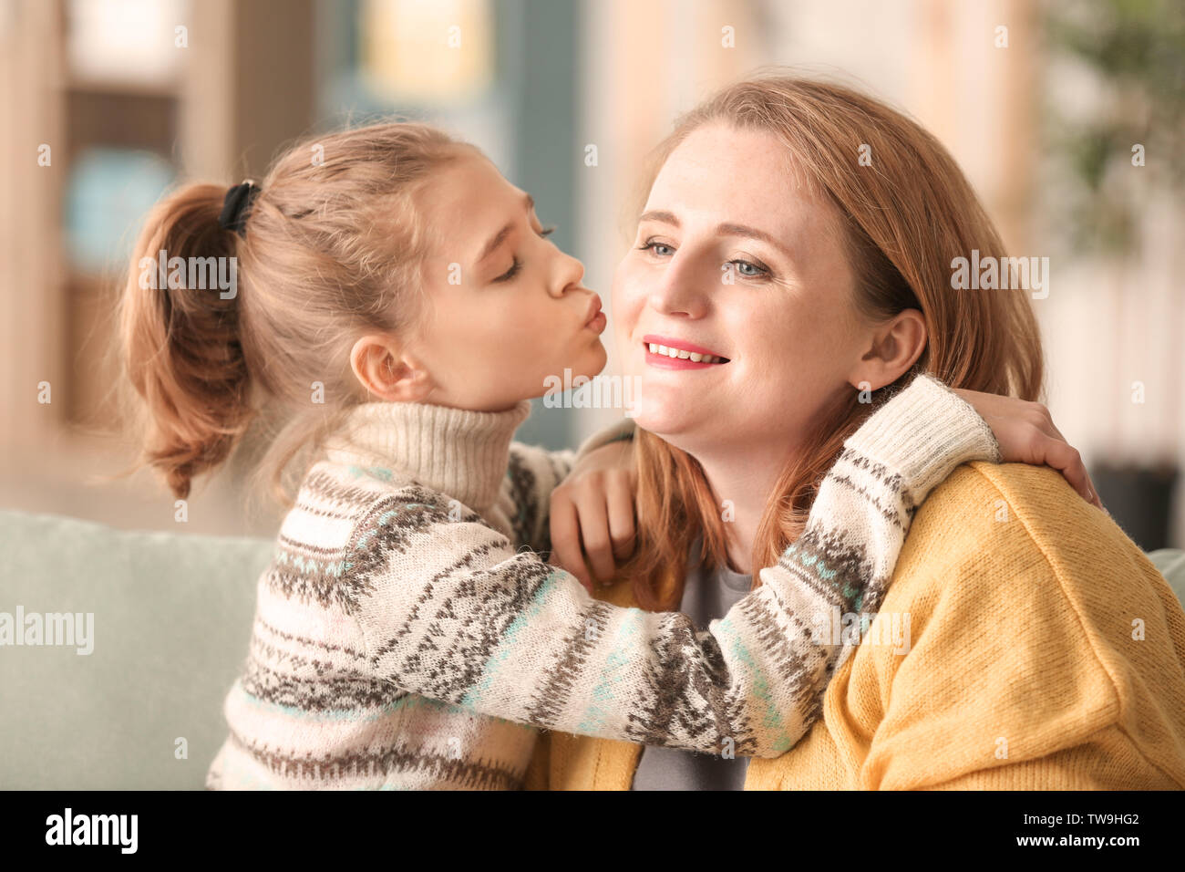 Cute little girl kissing her mother at home - Stock Image