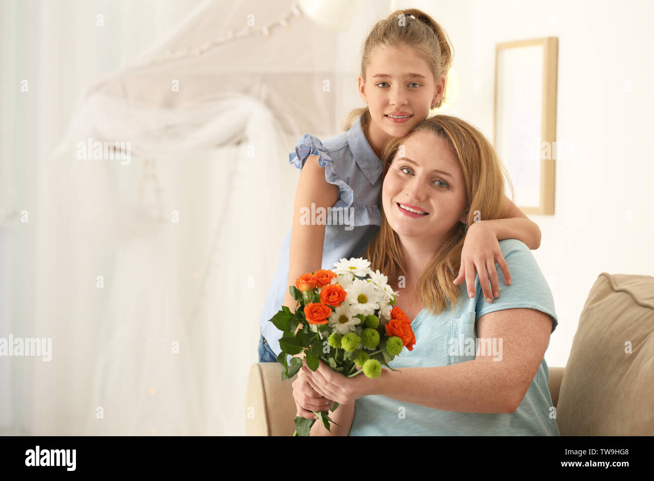 Portrait of happy mother and daughter with bouquet of flowers at home - Stock Image