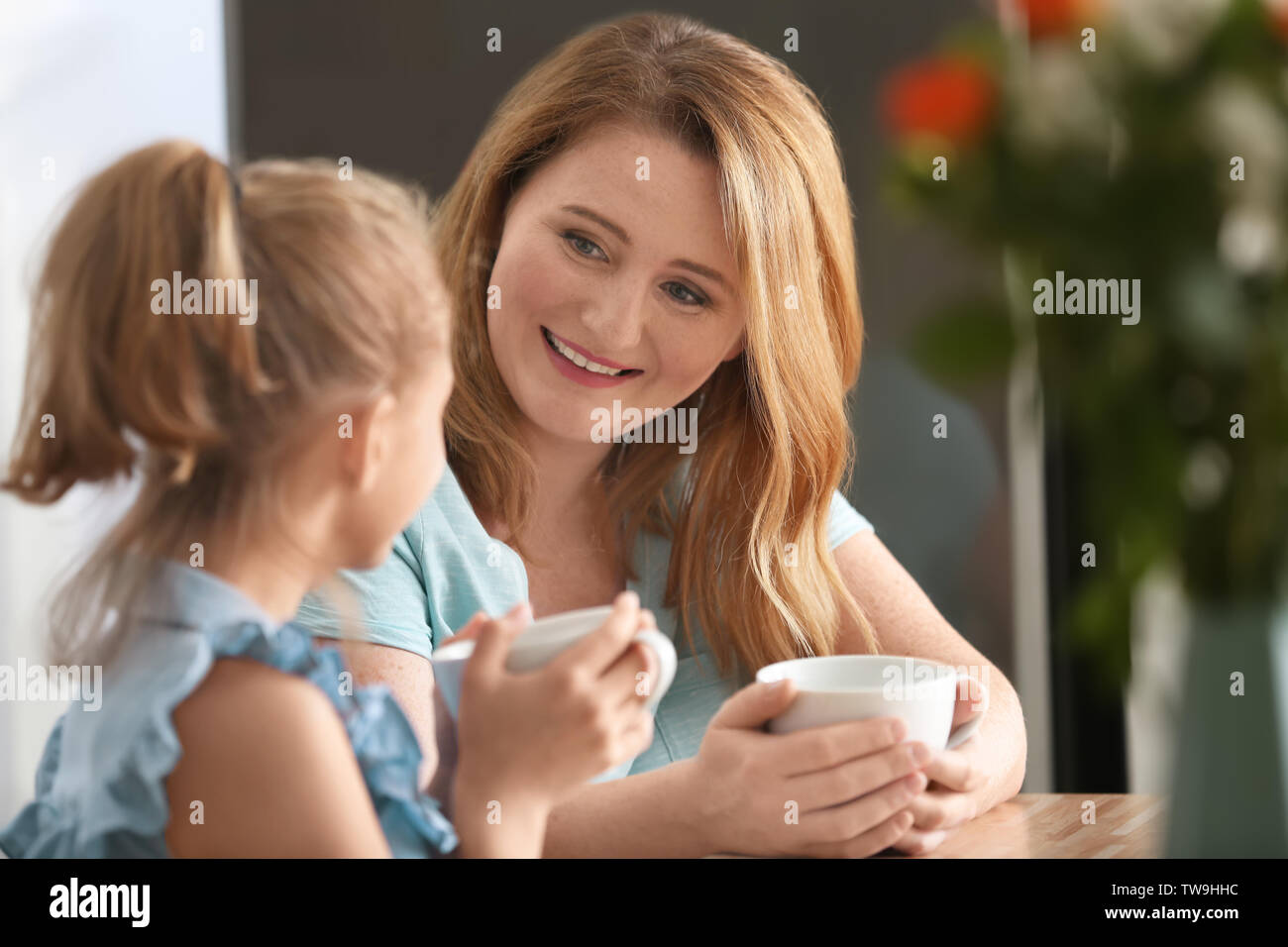 Happy mother and daughter drinking tea in kitchen - Stock Image