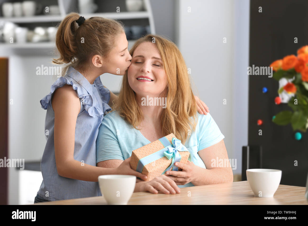 Cute little girl giving her mother a present in kitchen - Stock Image