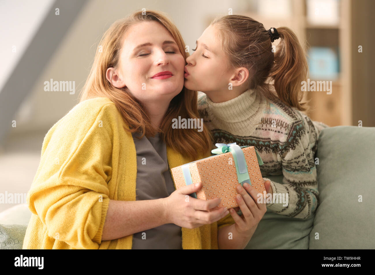 Cute little girl giving her mother a present at home - Stock Image