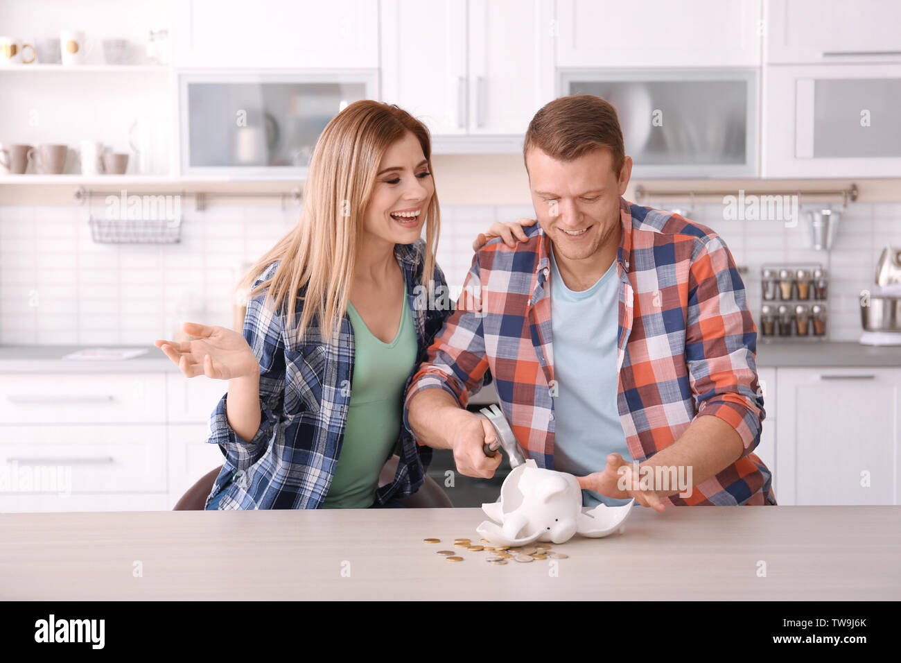 Young couple breaking piggy bank with hammer at home - Stock Image