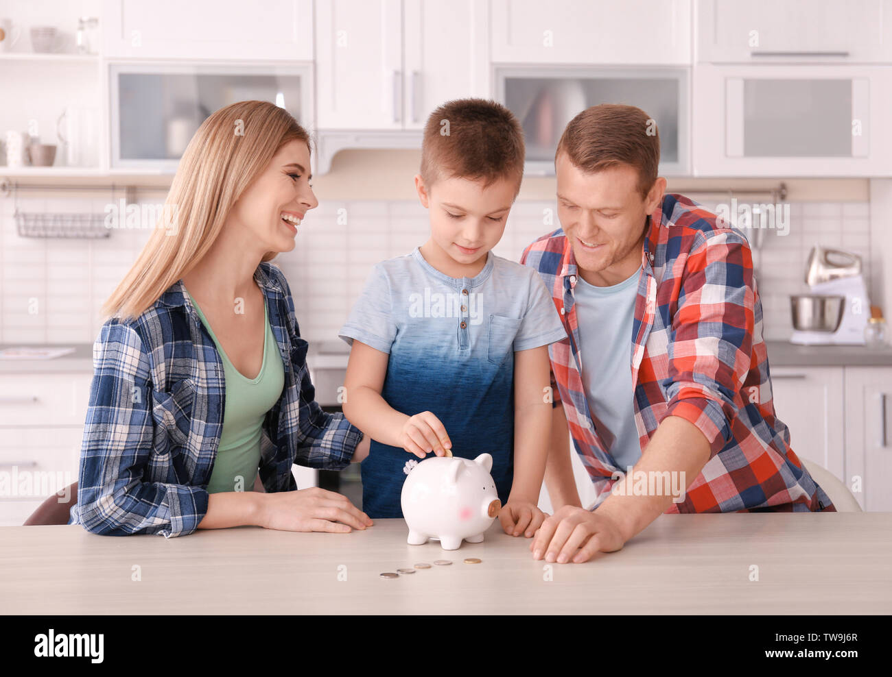 Happy family putting coin into piggy bank  at home - Stock Image