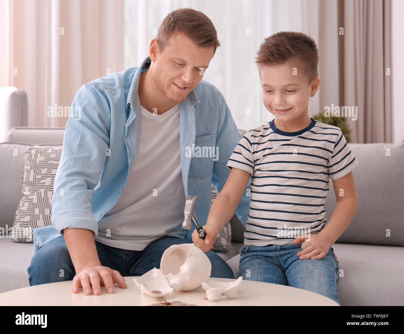 Father with little son breaking piggy bank with hammer at home - Stock Image