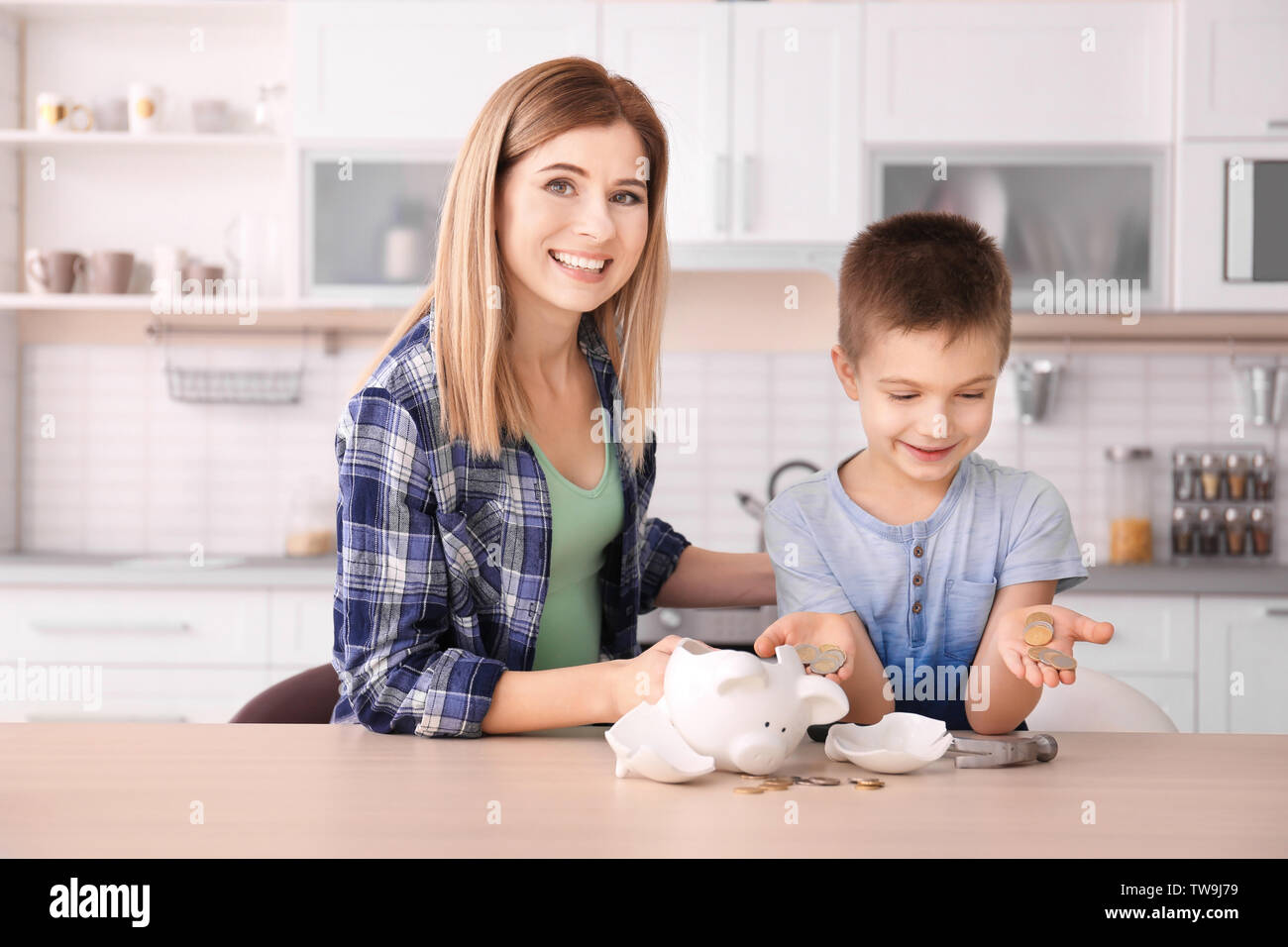 Mother and little son with broken piggy bank on table at home - Stock Image