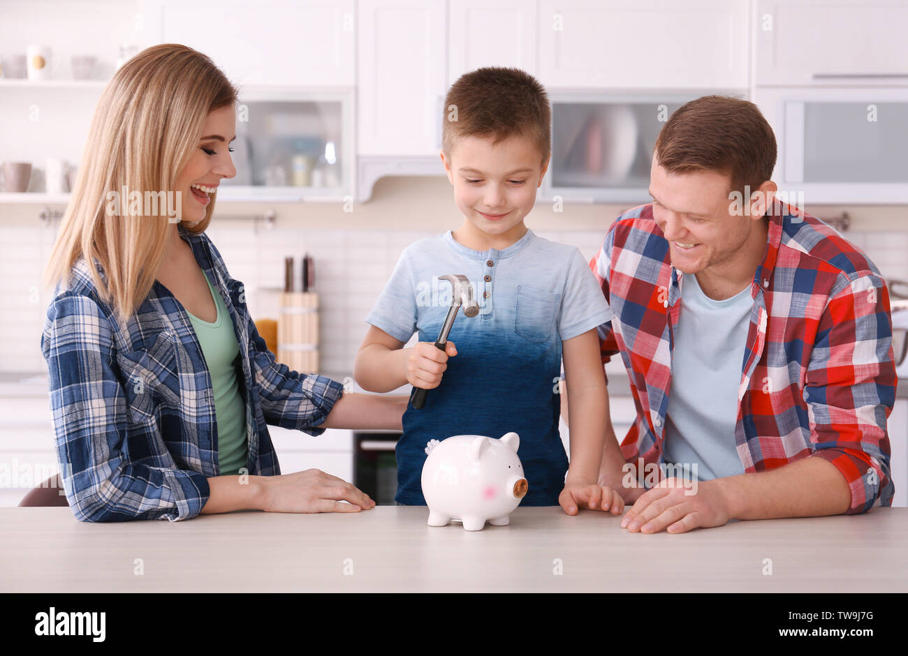 Happy family breaking piggy bank with hammer at home - Stock Image
