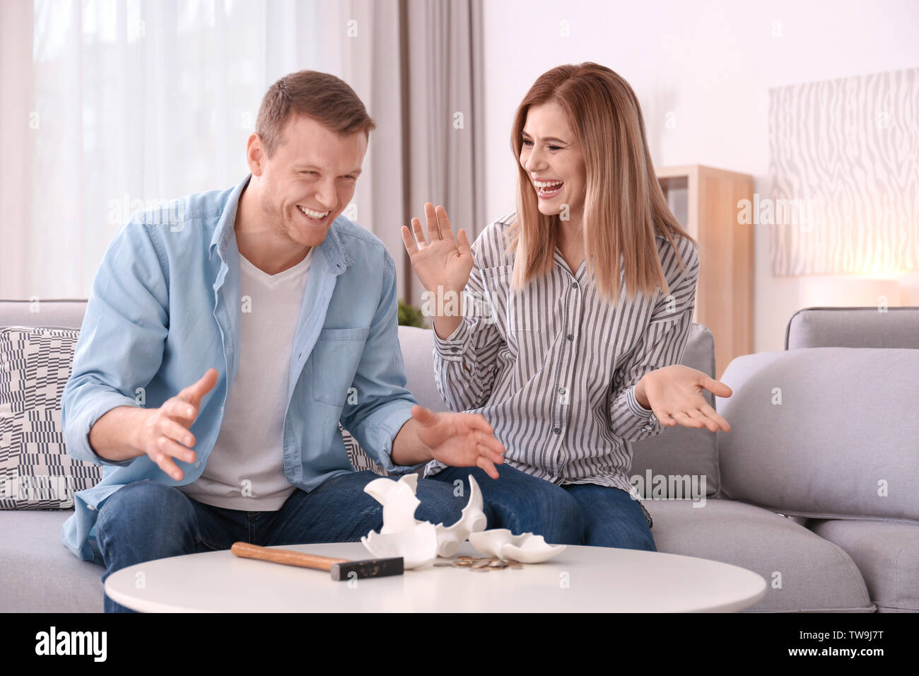 Happy young couple with broken piggy bank at home - Stock Image