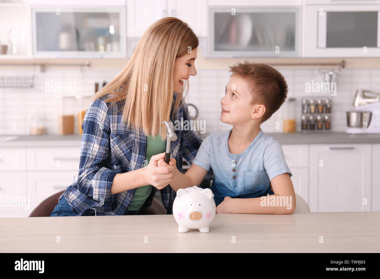 Mother with little son breaking piggy bank with hammer at home - Stock Image