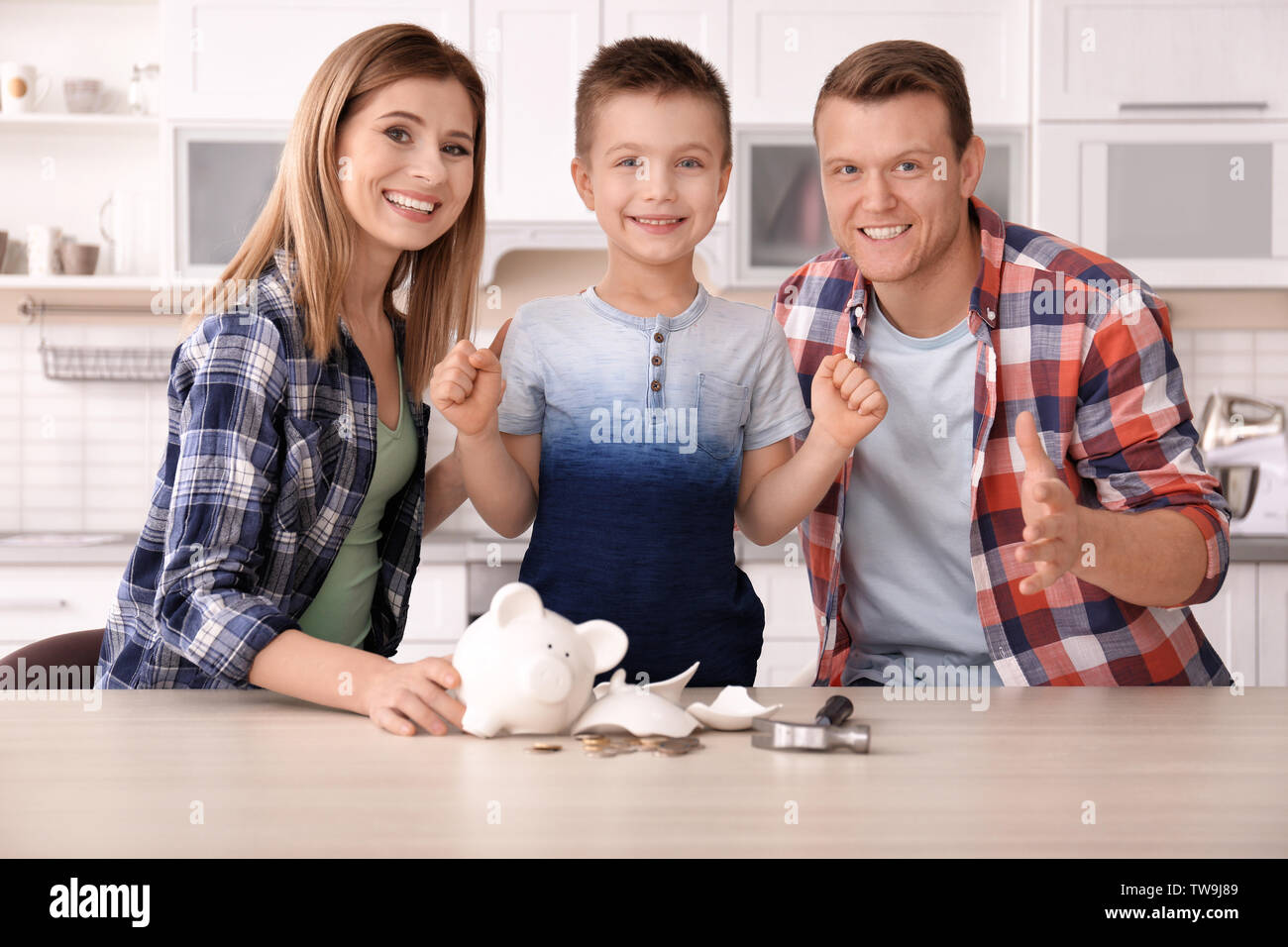 Happy family with broken piggy bank at home - Stock Image