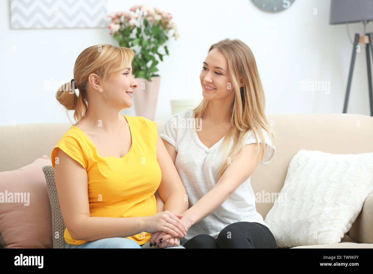 Young woman spending time with her mother at home - Stock Image