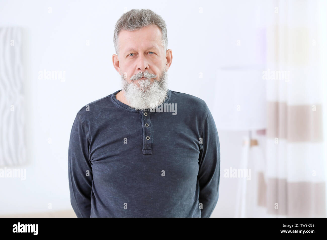 Portrait of mature man in casual clothes indoors - Stock Image