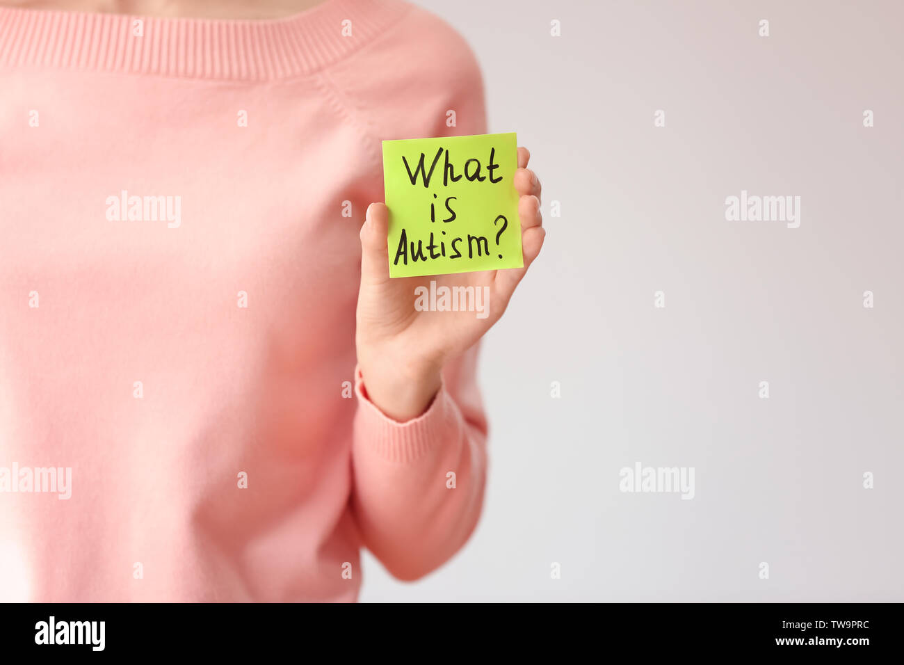 Woman holding note with phrase 'What is autism?' on light background - Stock Image