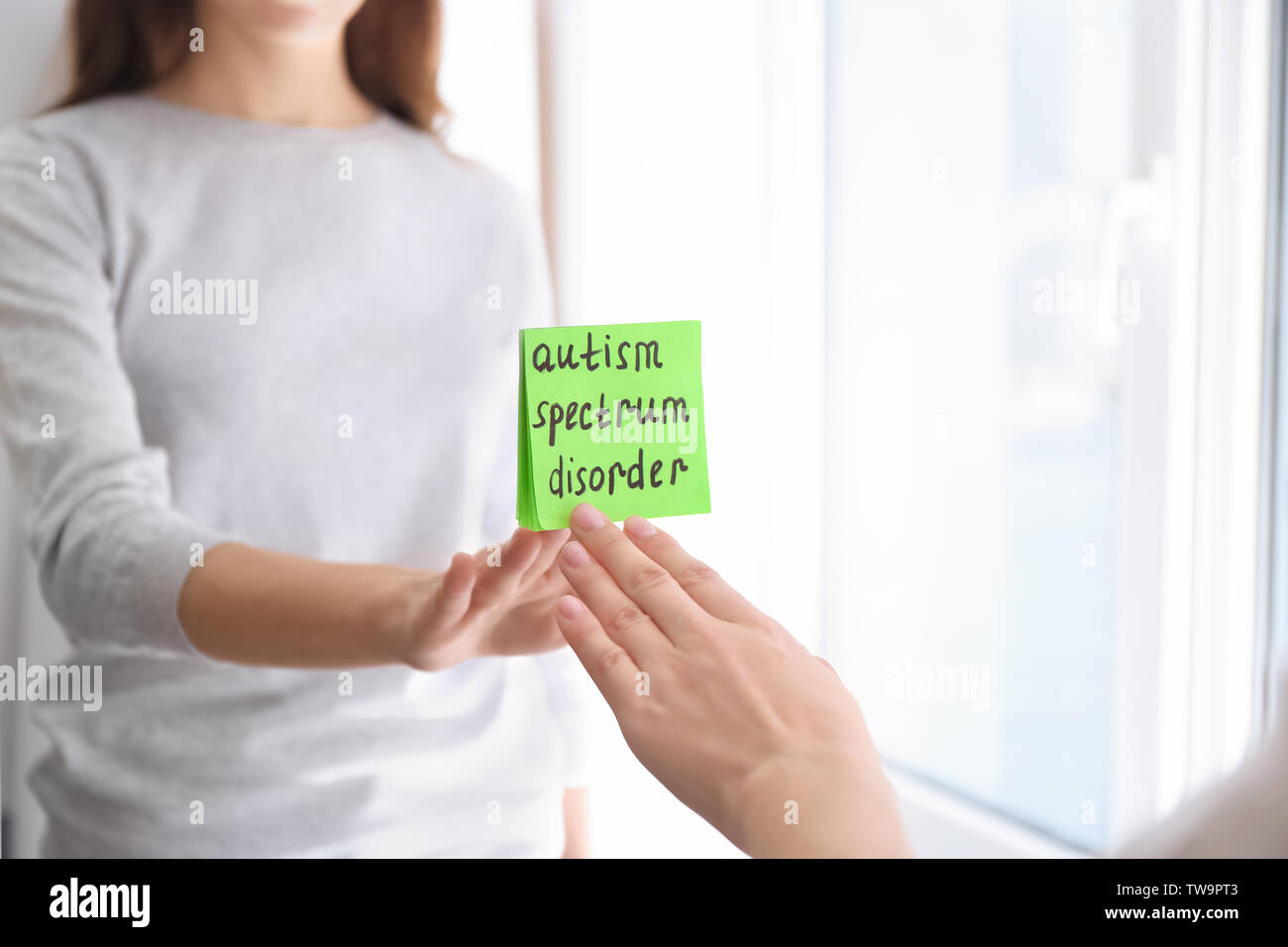 Woman sticking note with phrase 'Autism spectrum disorder' on mirror indoors - Stock Image