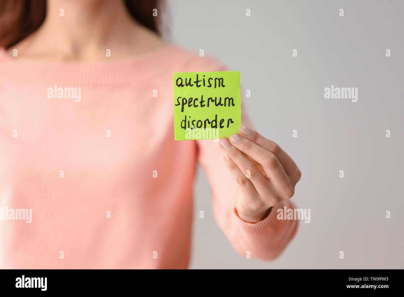 Woman holding note with phrase 'Autism spectrum disorder' on light background - Stock Image